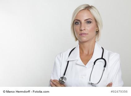 rztin im weissen Kittel und Stethoskop mit verschrnkten Arme